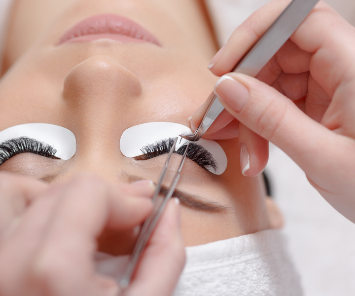 Permanent makeup. Eyelash Extension Procedure. Woman Eye with Long Eyelashes. Professional stylist lengthening female lashes. Eyelash extension procedure - master and a client in a beauty salon